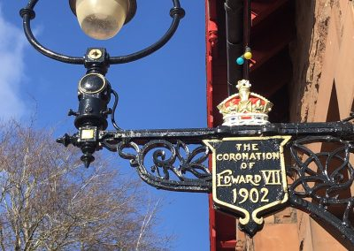 The two lamps by the North end doors were erected in 1902 for the Coronation of Edward VII. The commemoration lamps were restored in July 2017 by local painters J. & J. Tait, funded by the Community Council